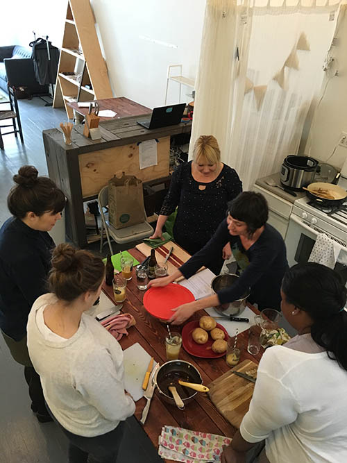 overhead photo of Becky Striepe teaching a cooking class in a studio kitchen