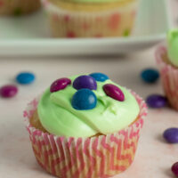 A close up of a cupcake with light green frosting topped with vegan M&M-style candy