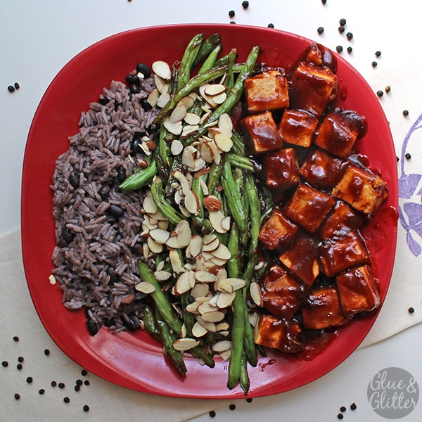 green beans on a red plate with BBQ tofu and beans and rice on the side