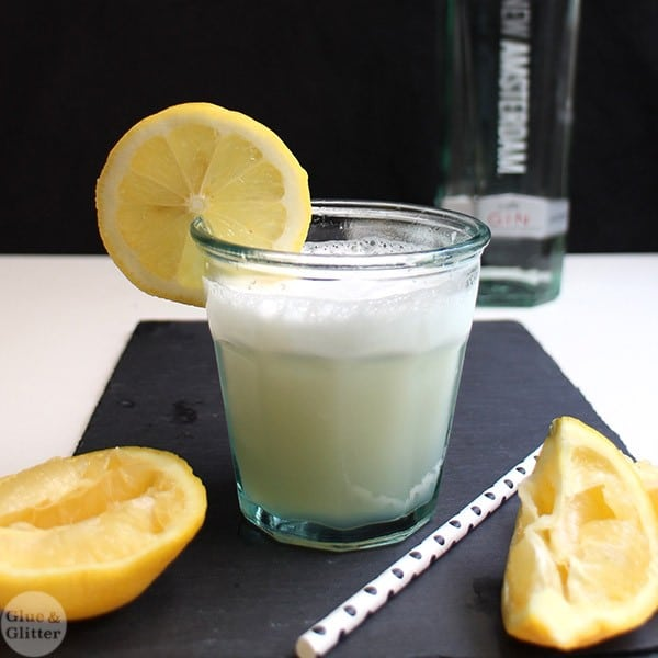 lemon gin flip cocktail on a slate tray with lemon wedges and a polkadot straw