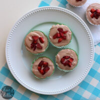 white serving plate of miniature vegan strawberry cheesecakes garnished with sliced strawberries