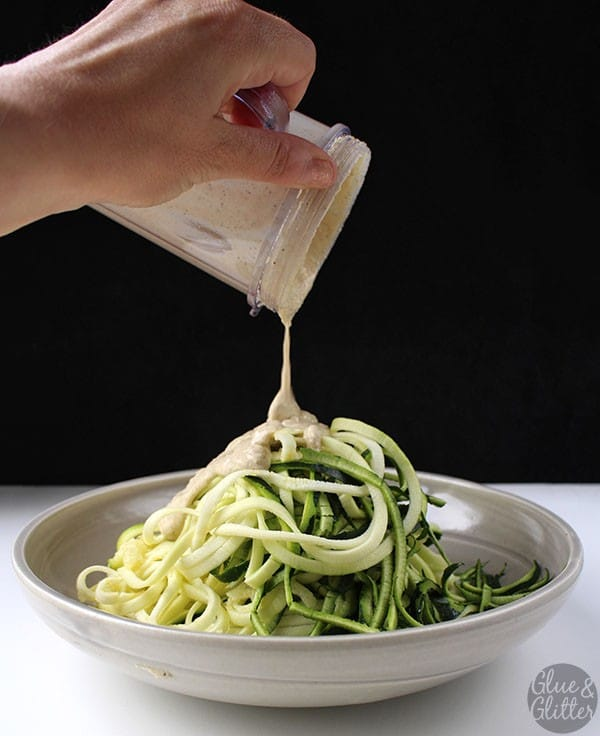 pouring salt and pepper sauce onto a bowl of zoodles