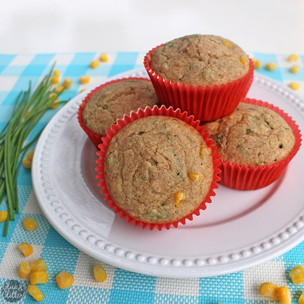 Simple vegan cornbread muffins with pieces of chive and whole corn kernels.