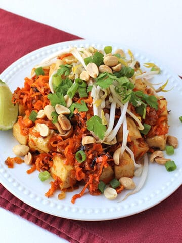 orange tofu over sweet potato noodles with peanuts, green onion, and bean sprouts, lime wedge on the side