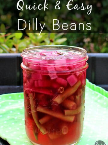 jar of pickled dilly beans on a table outside, text overlay