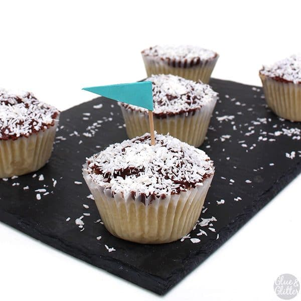 serving tray of vegan coconut cupcakes with chocolate frosting and shredded coconut on top. One cupcake has a tiny blue flag in it
