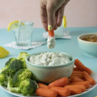 dipping a carrot into ranch party dip so you can see how thick and creamy it is