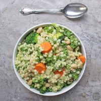 Israeli couscous salad with white beans and a mix of raw and lightly steamed veggies in homemade, creamy avocado-lemon dressing.
