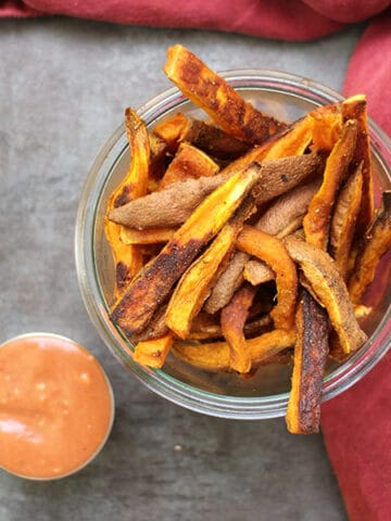 overhead photo of a serving container of sweet potato fries next to creamy dipping sauce