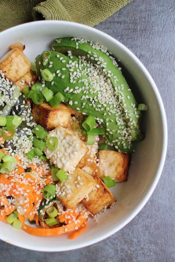 Seaweed Salad in a bowl with air fryer tofu, avocado, veggies, and sesame seeds