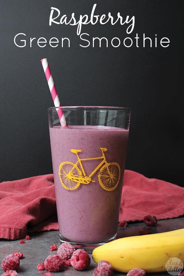 a raspberry green smoothie in a pint glass with a yellow bicycle printed on it next to frozen berries and a banana, text overlay