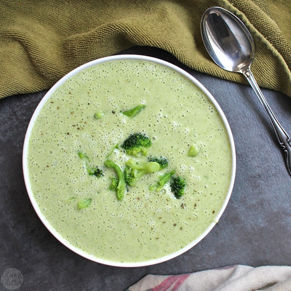 overhead photo of vegan cream of broccoli soup with steamed broccoli garnish