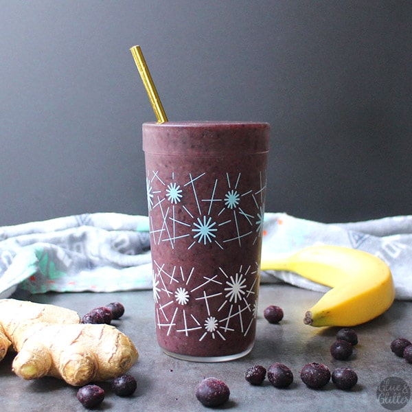 close-up of a ginger blueberry smoothie in a glass with ingredients on the table