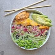 overhead photo of a spicy sushi bowl with edamame, vegetables, sesame seeds, mango, and avocado