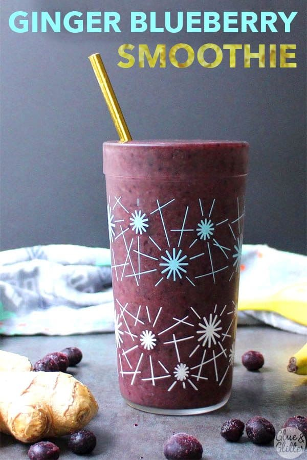 blueberry green smoothie on a slate table with a gold straw and text overlay