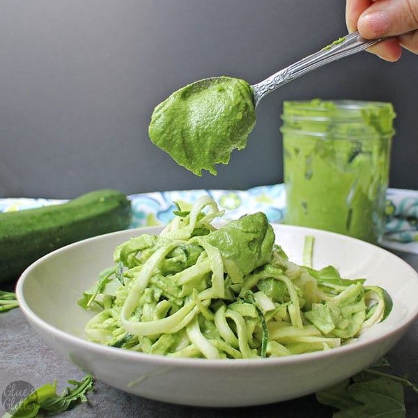 Spooning arugula pesto over a bowl of zoodles