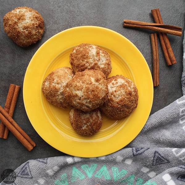 plate of air fryer donut holes on a slate table with cinnamon sticks