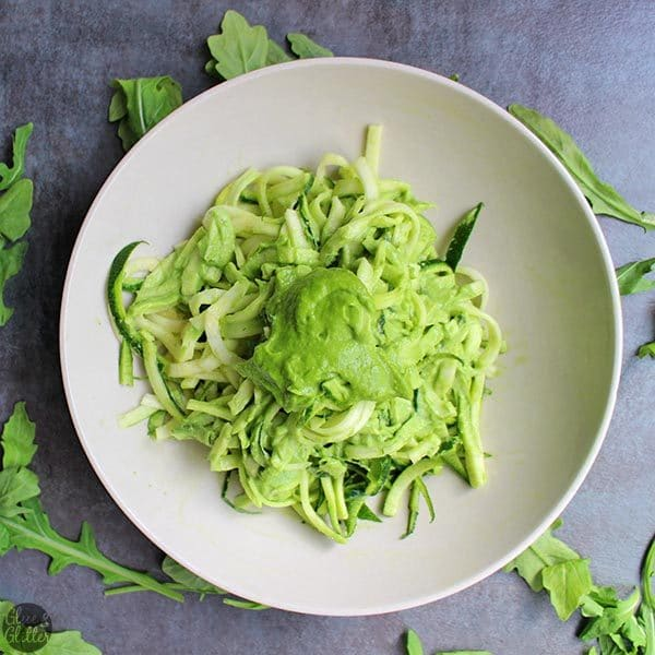 Bowl of zoodles on a slate table with arugula pesto on top
