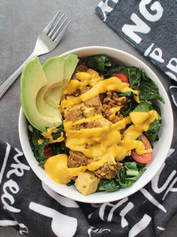 overhead photo of a breakfast kale salad with vegan bacon, tofu, vegan cheese sauce, and sliced avocado