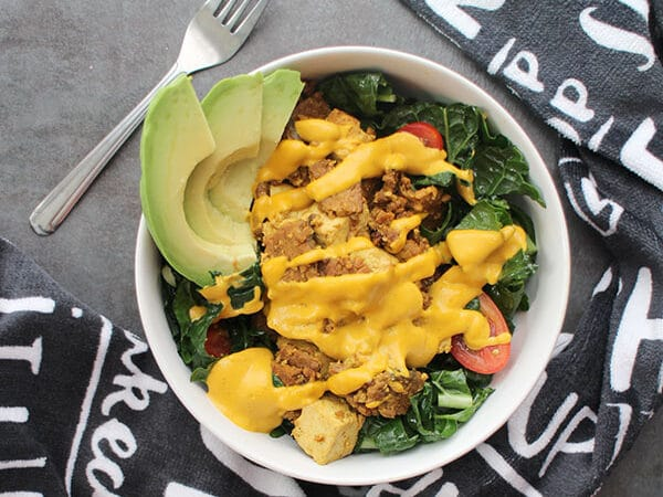overhead photo of a breakfast kale salad with vegan bacon, tofu, vegan cheese sauce, and sliced avocado