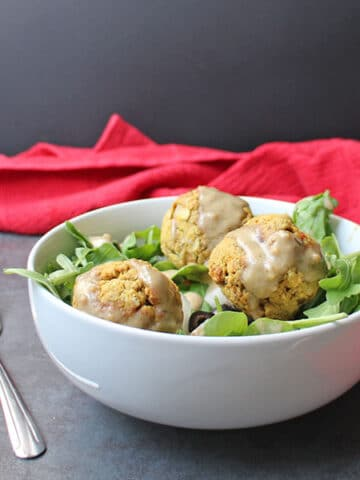 a green salad with air fryer falafel on top drizzled with tahini dressing