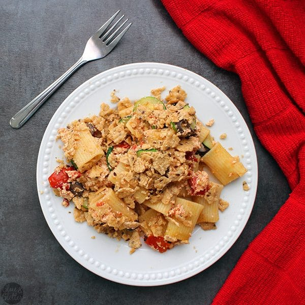 A plate of vegan rigatoni casserole, topped with crushed rice crackers