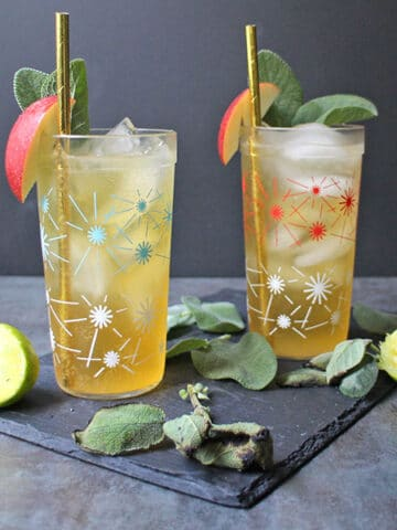 pair of glasses with ice and hard apple cider cocktail garnished with sage and an apple slice