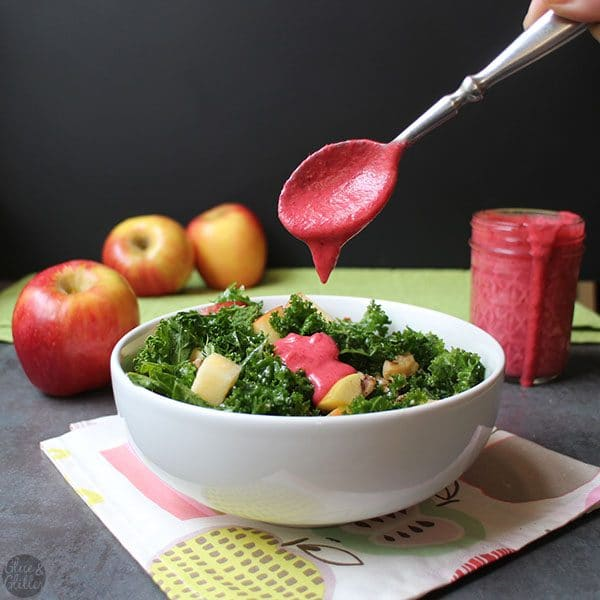 spooning hot pink cranberry dressing onto a bowl of of holiday kale salad with apples