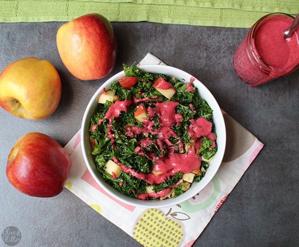 overhead photo of holiday kale salad with apples and a swirl of hot pink cranberry dressing