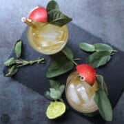 overhead photo of glasses with ice and hard apple cider cocktail garnished with sage and an apple slice