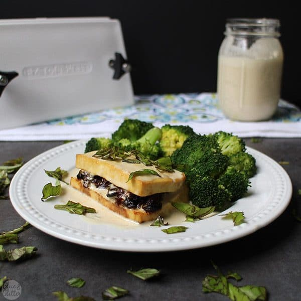 a plate of steamed broccoli and a tofu cutlet, sliced almost in half and stuffed with sun dried tomatoes and cream sauce