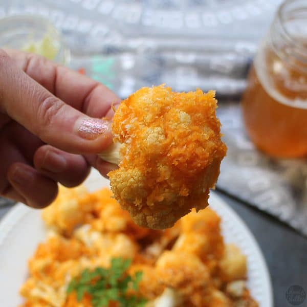 close-up of a hand holding a piece of air fryer buffalo cauliflower. plate and a cold beer in the background
