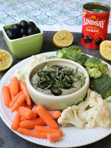 overhead photo of olive dip in a bowl garnished with sliced olives and basil, veggies on a serving platter around it