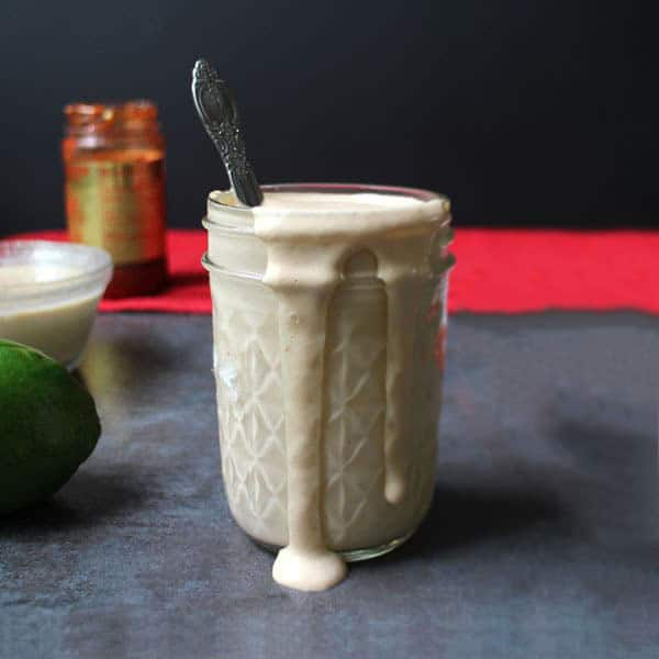 jar of spicy tahini dressing on a slate table with ingredients in the background