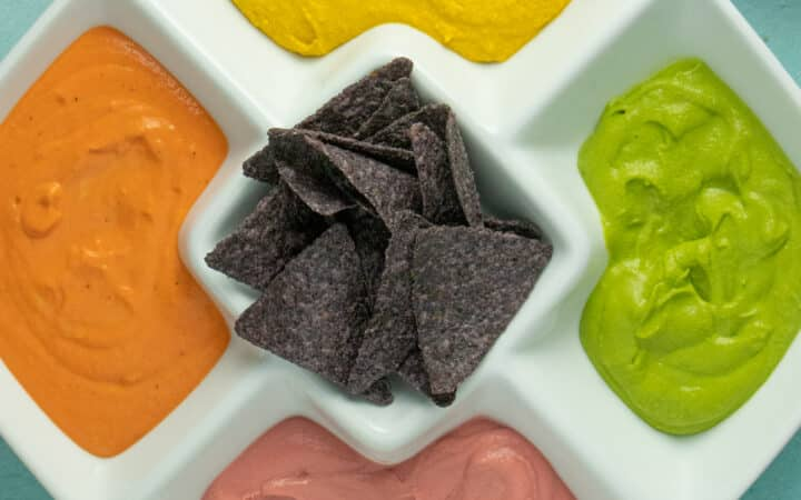 serving platter of 4 colors of hummus with blue corn chips in the center