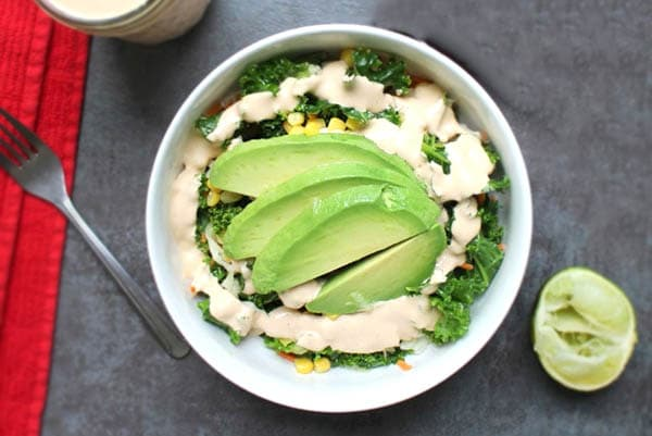spicy tahini sauce on a kale salad with avocado