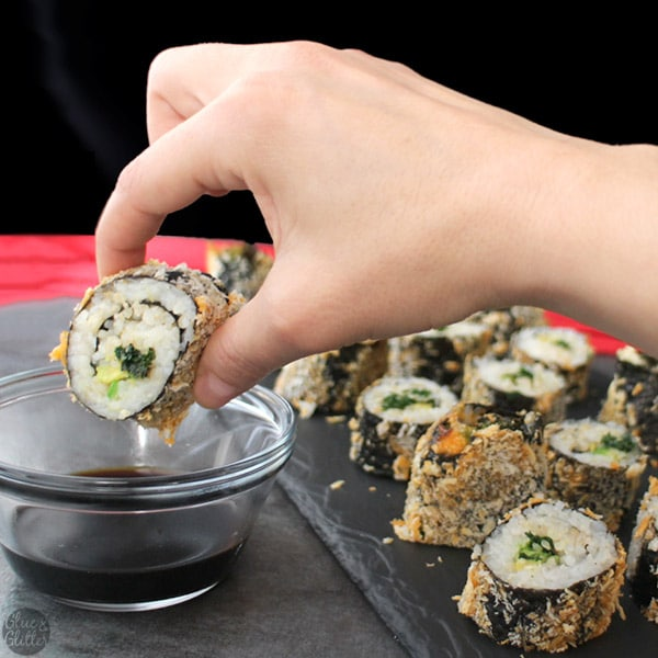 dipping a piece of air fryer sushi into soy sauce