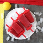 pile of cherry-lemon smoothie pops on a plate of ice cubes