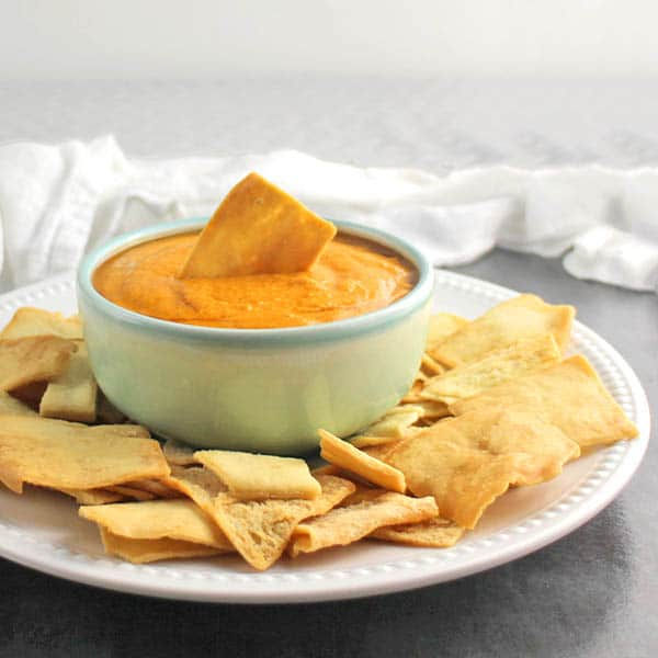 bowl of hummus with a pita chip dipped into it