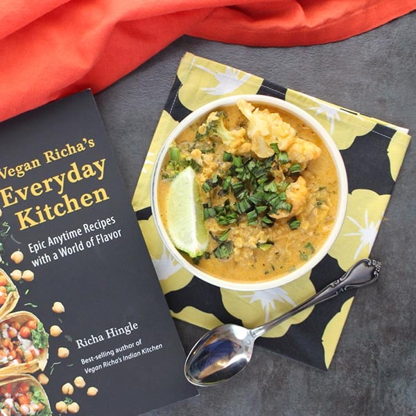 bowl of red curry soup on a floral napkin next to Richa's cookbook