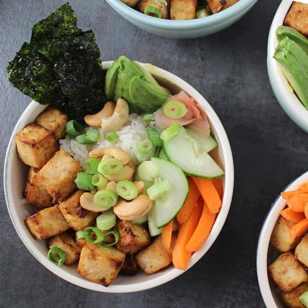 Sweet-and-spicy Ginger Tofu over sushi rice with my favorite sushi roll fillings. You can make the tofu in the oven or the air fryer!