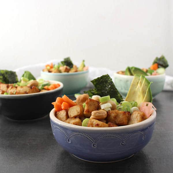 vegan sushi bowls in different colored bowls on a black tabletop