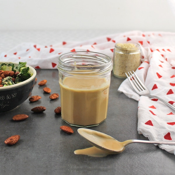 jar of vegan Caesar dressing on a slate table with a spoon