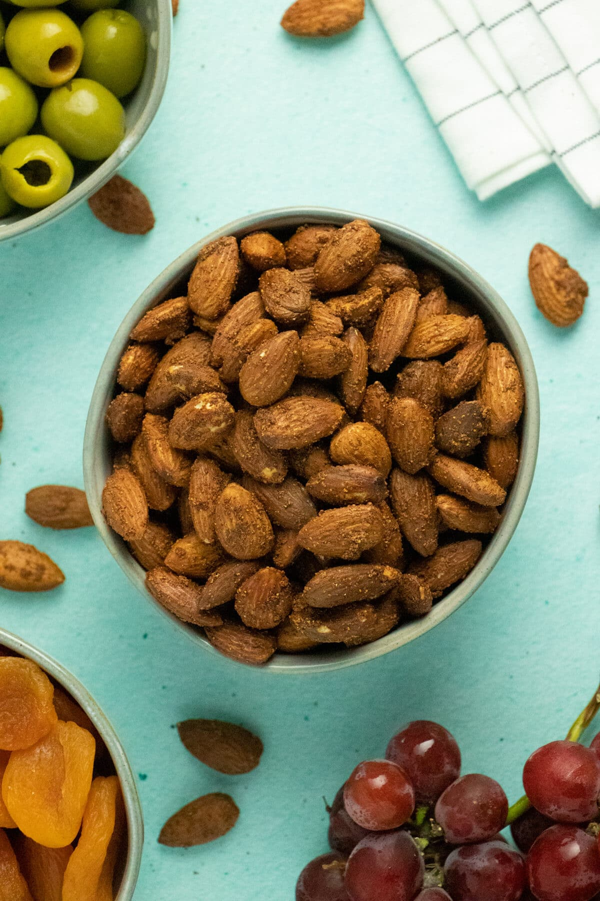 bowl of air fryer roasted almonds as part of a party spread with olives and dried apricots