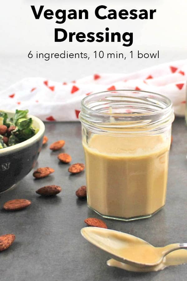 close-up of vegan Caesar dressing recipe in a jar next to a bowl of salad