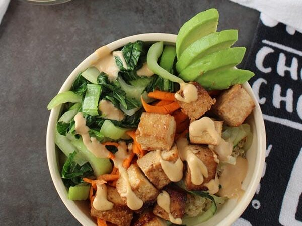 overhead photo of tofu bowl with vegetables on a gray table