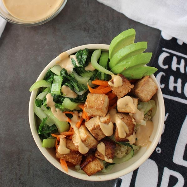 Baked Tofu Buddha Bowl - Firm, flavorful tofu baked to perfection on a bed of quinoa with a mix of fresh and cooked veggies. Top it off with creamy, Magical Tahini Dressing for an easy, satisfying meal in a bowl.