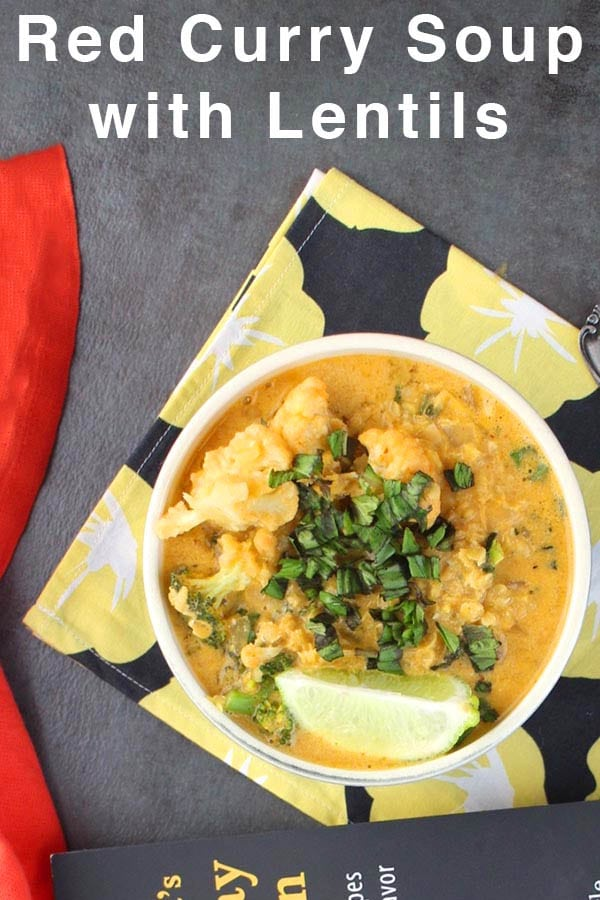 """overhead shot of red curry lentil soup on a floral napkin. Text reads: """"Red Curry Soup with Lentils"""""""