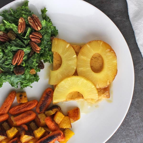 overhead close-up of pineapple glazed tofu on a white plate next to roasted vegetables and kale salad
