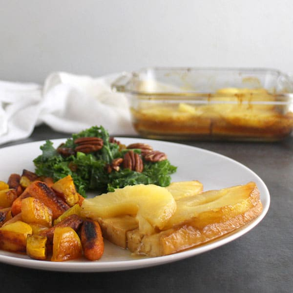 pineapple glazed tofu on a white plate next to roasted vegetables and kale salad
